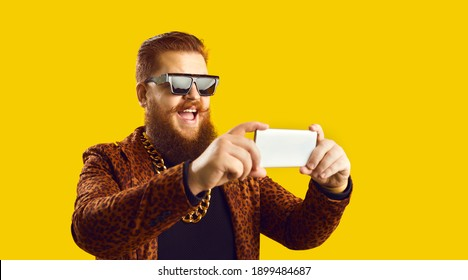 Celebrity live streaming, recording video or taking selfie on smartphone. Happy eccentric man in trendy glasses, extravagant rapper gold neck chain and leopard print jacket using mobile phone - Shutterstock ID 1899484687