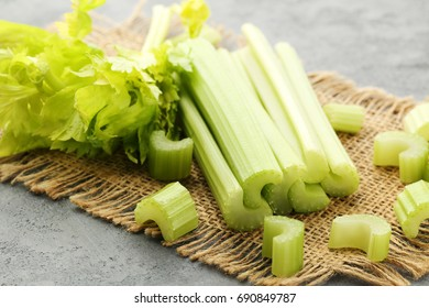 Celery with sackcloth on grey wooden table