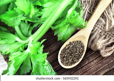 Celery seeds in spoon on wooden background, selective focus