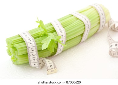 Celery with tape measure on the white background, concept of healthy nutrition and diet