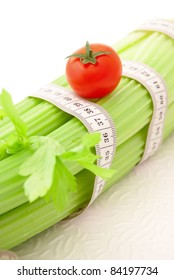 Celery and tomato with tape measure on the white background, concept of healthy lifestyle and diet