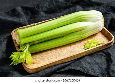 Celery vegetable on wood tray. Black background. Top view