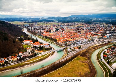 Celje, Slovenia. Car traffic in Celje, Slovenia. Bridge over the Savinja river. Aerial view of city historical center from the castle. Cloudy day with mountains