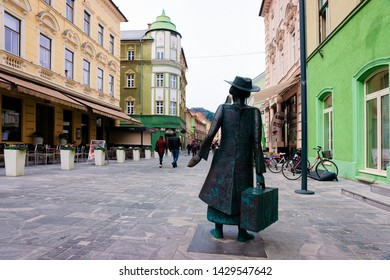 Celje, Slovenia - March 27, 2019: Cityscape with Woman statue with bag in the street of Celje old town in Slovenia. Building architecture in Slovenija. Travel