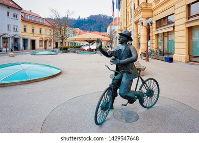 Celje, Slovenia - March 27, 2019: Sculpture of man with photo camera on bicycle at National Hall in the center of Celje old town in Slovenia. Building architecture in Slovenija.