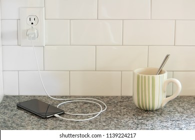 a cell charging on a counter top near a striped coffee mug or tea cup with a spoon in it, white subway tile background