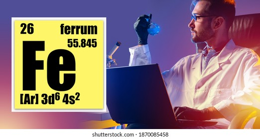 Cell with ferrum properties from periodic table. Man is working with the ferrum element. FE logo in yellow cell. Laboratory assistant with a laptop examines the properties of ferrum.