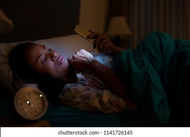 Cell Phone Addict Woman Awake Late at Night on Bed Using Smartphone For Chatting, Searching and Sending Text Message in Internet Addiction and Mobile Abuse Concept. Digitals Lightning on Face.