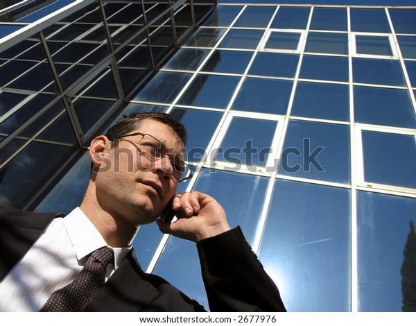 Cell phone communication.Young businessman talking to the cell phone in front of an office  .