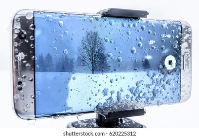 Cell phone covered in ice and water being used to shoot video in a cold snow storm.