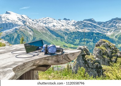 cell phone with headphones on a wooden table on the background of the Swiss Alps and mountain scenery.