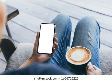 cell phone Mockup image blank white screen.woman hand holding texting using mobile on desk at coffee shop.background empty space for advertise text.people contact marketing business,technology