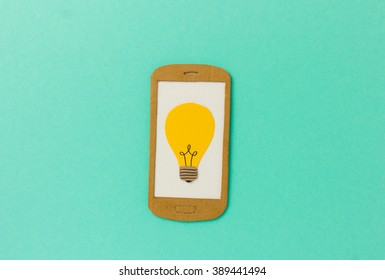 Cell phone paper model with light bulb symbol - image concept for e-learning, online classes, research tools