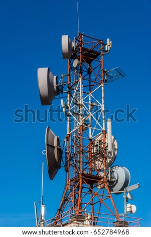Cell phone relay tower in a bright sunny day. Clear blue sky in the background.