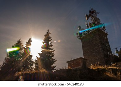 Cell phone relay tower on the mountain. Sunlight between some fir trees. Mountain cable transport on background.