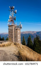 Cell phone relay tower on hill. Mountains seen in the background.