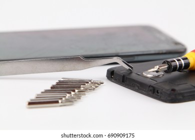 Cell phone repair. Smartphone parts and tools for recovery, selective focus.