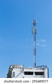 Cell phone tower on building with blue sky.