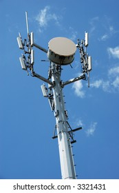 Cell phone tower over blue sky with few clouds.