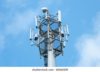 Cell  phone tower rises against a blue sky.