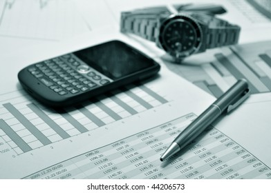 Cell phone, watch and pen on a market report