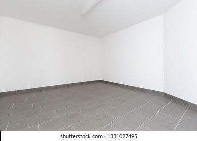 Cellar with gray tiles and white walls. Nobody inside