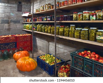 Cellar inside with vegetables and row of jars on shelves
