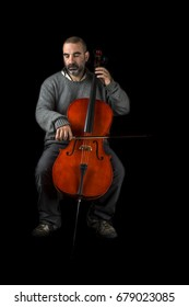 Cellist playing his instrument on black background