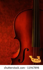 Cello, against canvas background.  Luscious warm tones enhance the beauty of this instrument.