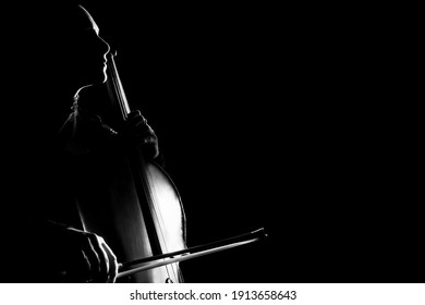 Cello classical music cellist player. Cellist with musical instrument in darkness