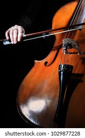 Cello player. Cellist hands playing cello with bow. Violoncello orchestra musical instrument closeup