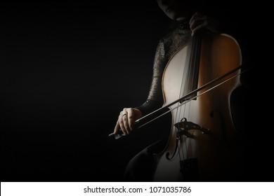 Cello player. Cellist hands playing cello with bow orchestra musical instrument closeup