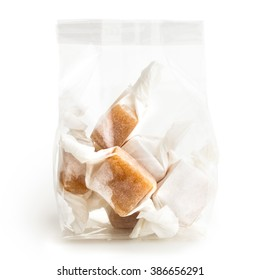 Cellophane packet of wrapped caramel toffees isolated on white.