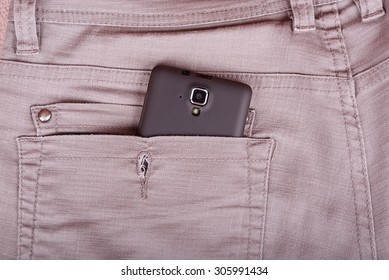Cellphone in trousers back pocket, detail