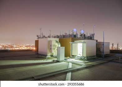 Cellular, Base Radio station on the roof of building at night time.