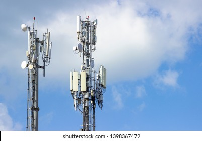 Cellular Base Station or Base Transceiver Station. Telecommunication tower. Wireless Communication Antenna Transmitter. 3G, 4G and 5G Cell Site with cloudy blue sky.