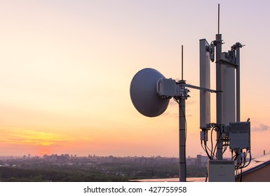 cellular communications tower on a background of the city and a beautiful sunset in summer
