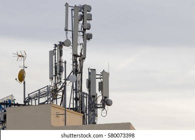 Cellular phone antennas on a building roof.