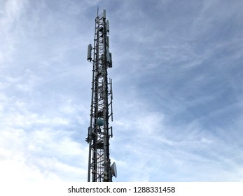 Cellular Radio Transmitter Cell Phone Tower with Blue Sky and Clouds