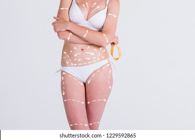 Cellulite removal scheme. White markings on girl body smooth skin.