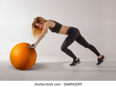 Cellulite treatment Concept. Young woman holding orange