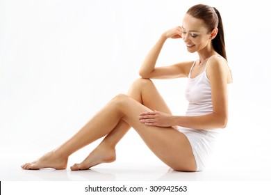 Cellulite. A woman checks the stretch marks on legs. The beauty of the female body, natural woman ,young woman in white lingerie