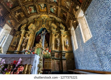 CELORICO DA BEIRA, PORTUGAL – July 20, 2018:  Main chapel with a magnificent altarpiece, painted coffered ceiling and walls covered in traditional blue and white tiles, of the church of Saint Mary