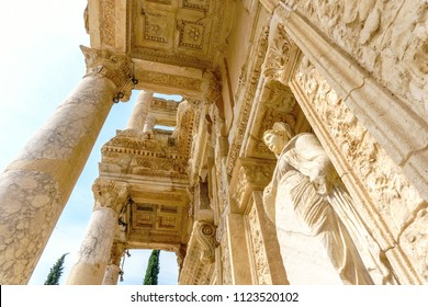 Celsus library and sculpture in Ephesus ancient city ruins on cloudy sky in Izmir, Turkey.