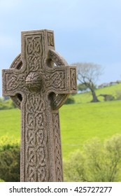 Celtic Cross Against Green Fields and Stormy Skies, England.