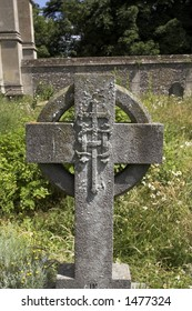 A celtic cross gravestone in a country churchyard
