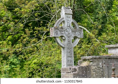 a celtic cross in an old and well hidden cemetery in northern ireland