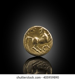 Celtic gold stater. Old Celtic coin showing horse, exposed on black reflecting glass, found in life dig by metal detector.England.