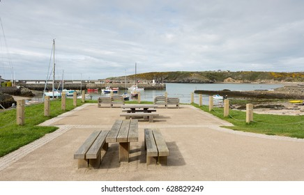 CEMAES BAY HARBOUR - APRIL 15th 2017: Cemaes Bay harbour in Anglesey, North Wales with picnic area in foreground. Cemaes Bay Harbour, UK April 15th, 2017