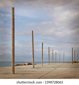 Cement beach with wooden poles and the sea in the background